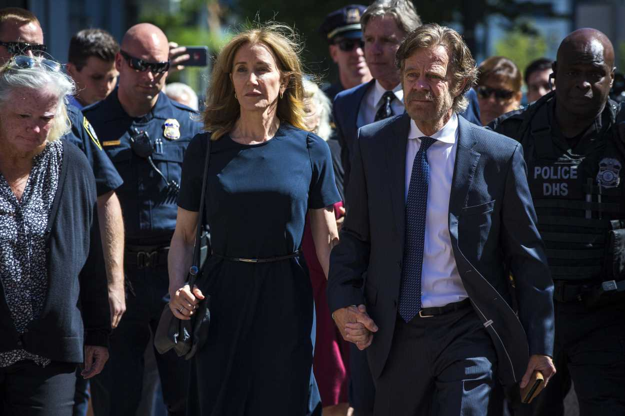 Felicity Huffman arrives to sentencing in college admissions scandal holding hands with her husband